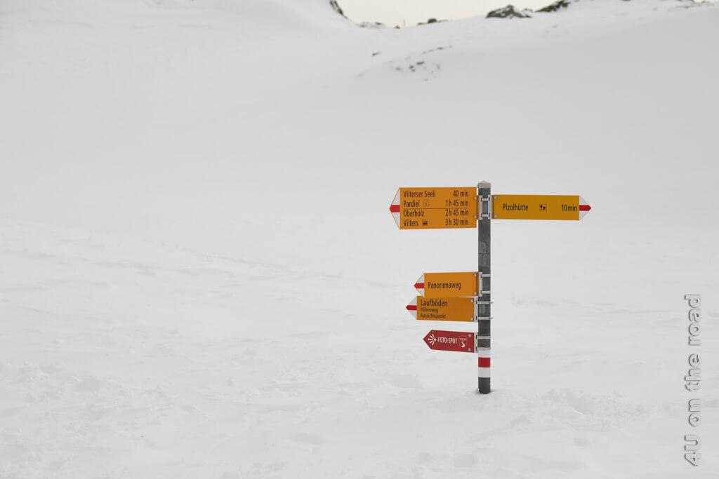 Der Wegweiser zeigt es, die Schneetiefe ist unberechenbar. Mal sieht man den blanken Boden, weil der Wind den Schnee davon getragen hat und woanders versinkt man wieder darin.