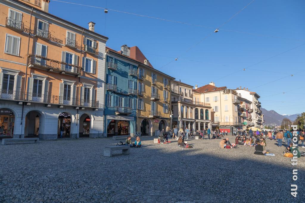 Piazza Grande im letzten Sonnenschein des Tages und Leute, die auch ohne Sitzgelegenheit das Leben geniessen. - Frühling in Locarno