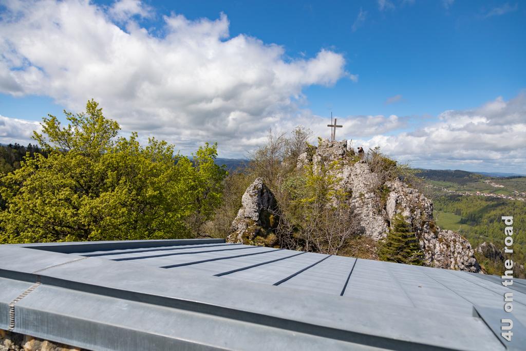 Blick über das Dach der Schutzhütte auf das Gipfelkreuz.