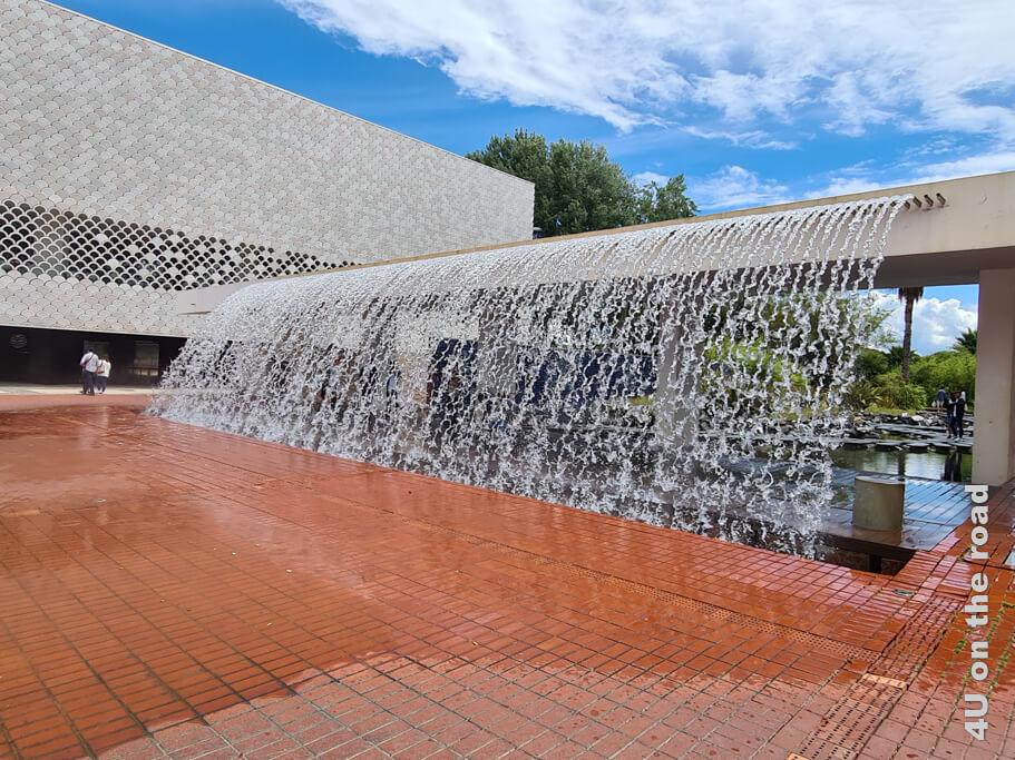 Als wir ankommen, hat es aufgehört zu regnen. Trockenen Fusses kann man hinter dem Wasserfall zum Oceanarium laufen. Das Gebäude selbst besteht aus lauter Fischschuppen. - Sehenswürdigkeit von Lissabon
