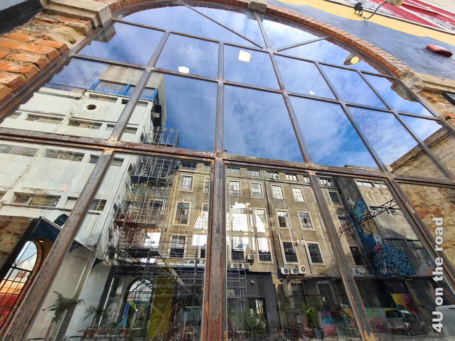 Spiegelung im Fenster eines Clubs mit Torwächter.