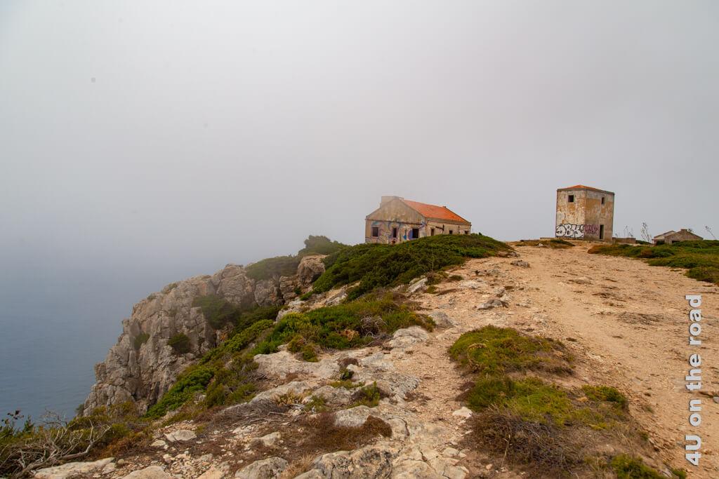 Von weitem sehen die Ruinen neben dem Leuchtturm von Cabo Espichel im Nebel interessanter aus.